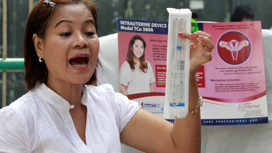 A medical worker explains a family planning method using the Intra Uterine device (IUD) to housewives in a local government health center in Navotas, Manila, March 3, 2011.