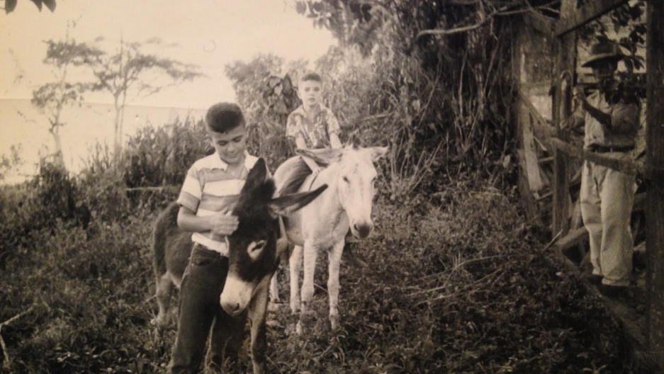 Brothers John and George Campbell ride donkeys in the forests of Segovia, Colombia.