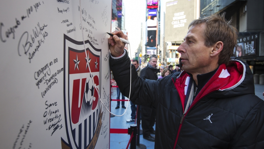 German soccer star Jurgen Klinsmann, the coach of the US men's national team, signs a board celebrating the 100th anniversary of the US national team in Times Square, April 4, 2013.