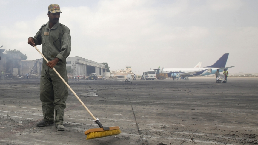 A man clears debris from the tarmac of Jinnah International Airport, after Sunday's attack by Taliban militants on Sunday, in Karachi June 10, 2014. Taliban militants disguised as security forces stormed into Pakistan's busiest airport on Sunday night, tr