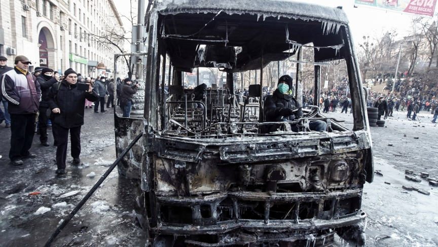 A pro-European integration protester sits in a burnt police bus after a rally near government administration buildings in Kiev January 20, 2014. With tension still high, about 1,000 protesters confronted police on Monday near Kiev's main government headqu