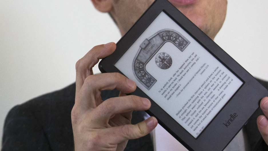 A journalist shows the new Kindle Voyage during a launch event in New York September 17, 2014.