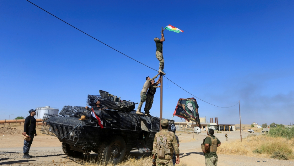 A member of Iraqi security forces takes down a Kurdish flag in Dibis on the outskirts of Kirkuk, Iraq, Oct. 17, 2017.