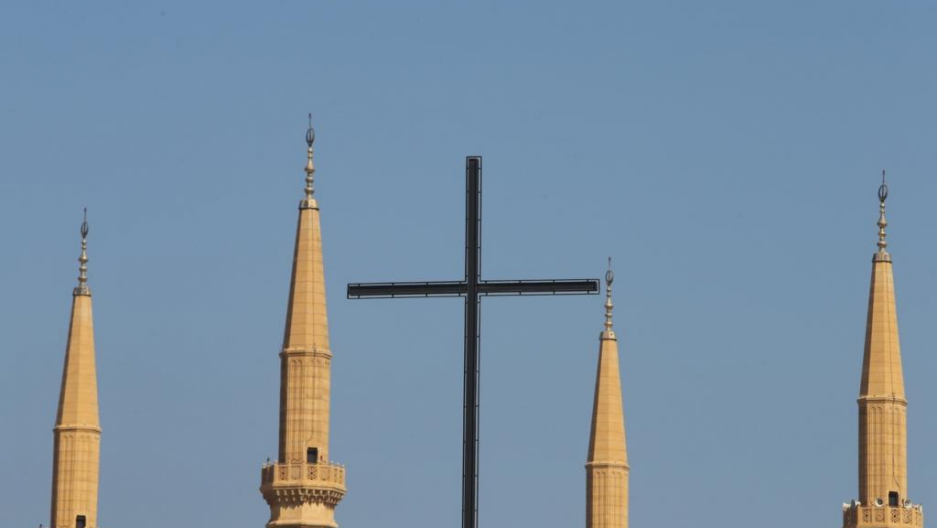 The cross of Beirut's Lazarite Church is flanked by the minarets of the Mohammed al-Amin Mosque in the Lebanese capital's downtown.