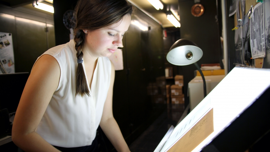 Lindsay Smith Zrull carefully places a glass plate photograph of the sky on a lightbox in the Plate Stacks room at the Harvard-Smithsonian Center for Astrophysics.
