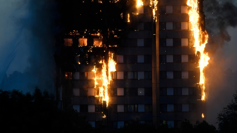 Flames and smoke billow as firefighters deal with a serious fire in a tower block at Latimer Road in West London.