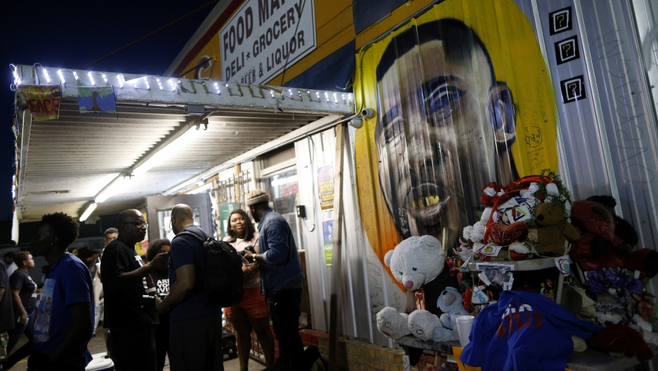 A mural of Alton Sterling is seen as people gather during a vigil