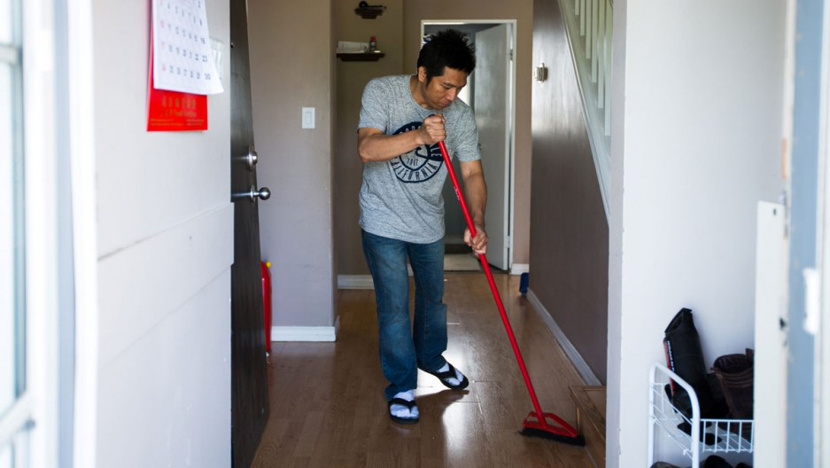 A man sweeps the floor of his house in Alberta, Canada.