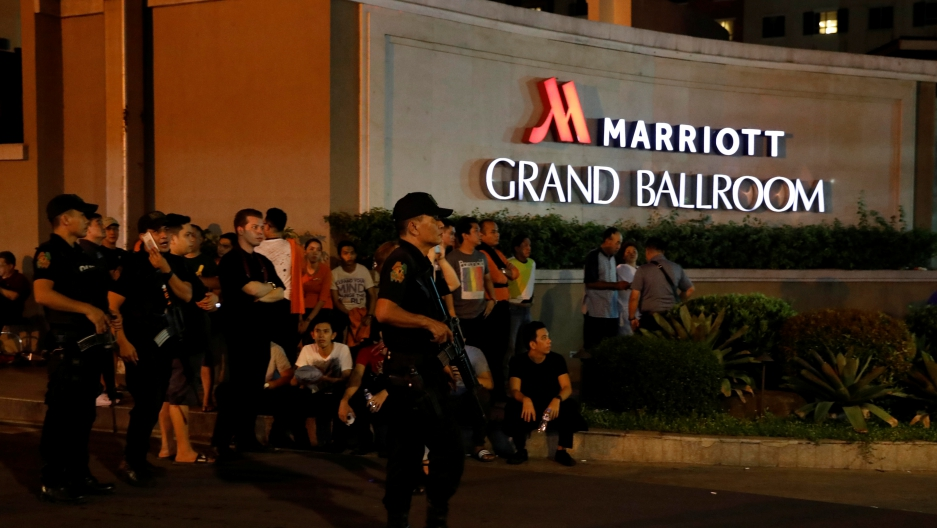 Policemen stand guard near evacuated employees of a hotel near a situation at a Resorts World building, in Pasay City, Metro Manila, Philippines.