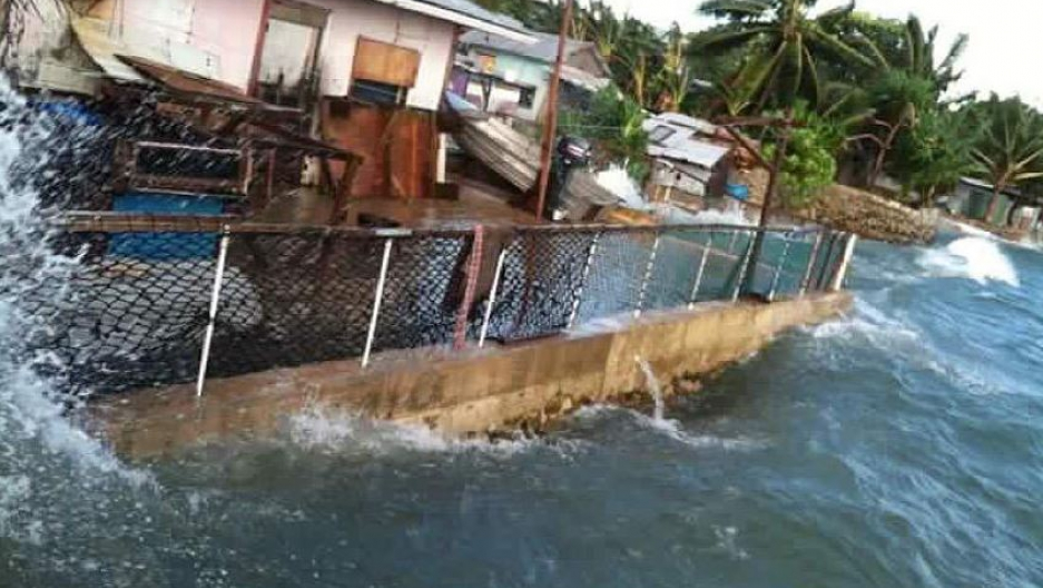 Ocean waves hit perilously close to a house in Majuro. Marshall Islands.