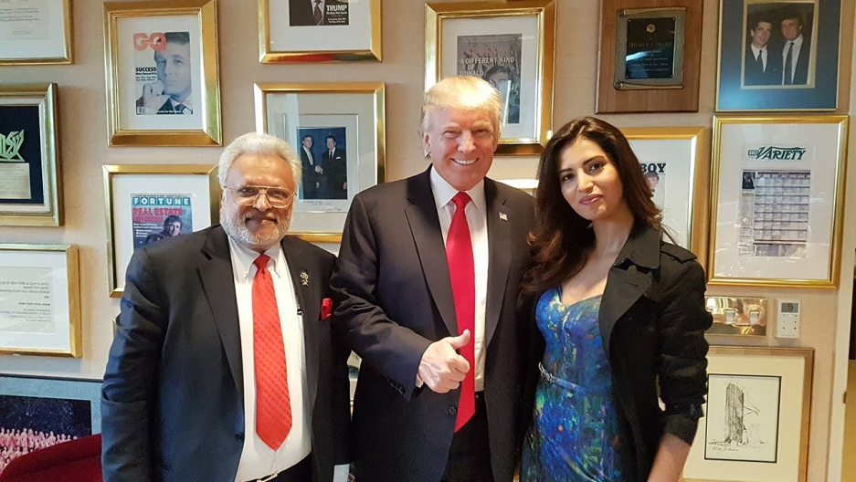 A man and a woman pose with Donald Trump in an office