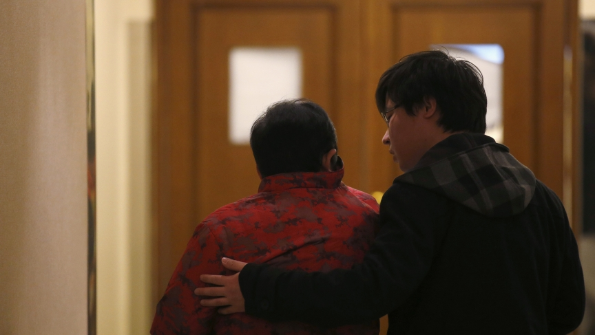 A man comforts a family member of a passenger onboard the missing Malaysia Airlines flight MH370 as they wait for news from Malaysia Airlines, at the lobby of a hotel in Beijing, March 14, 2014.