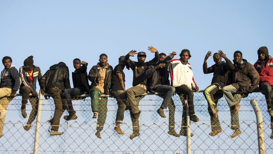 African migrants sit atop a border fence during an attempt to cross into Spanish territories, between Morocco and Spain's north African enclave of Melilla, Oct. 22, 2014.