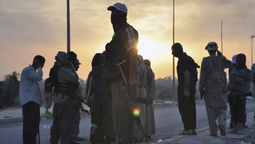 Fighters from the Islamic State of Iraq and Syria (ISIS) stand guard at a checkpoint in the northern Iraq city of Mosul on June 11, 2014. Since Tuesday, black clad ISIL fighters have seized Iraq's second biggest city Mosul and Tikrit, home town of former