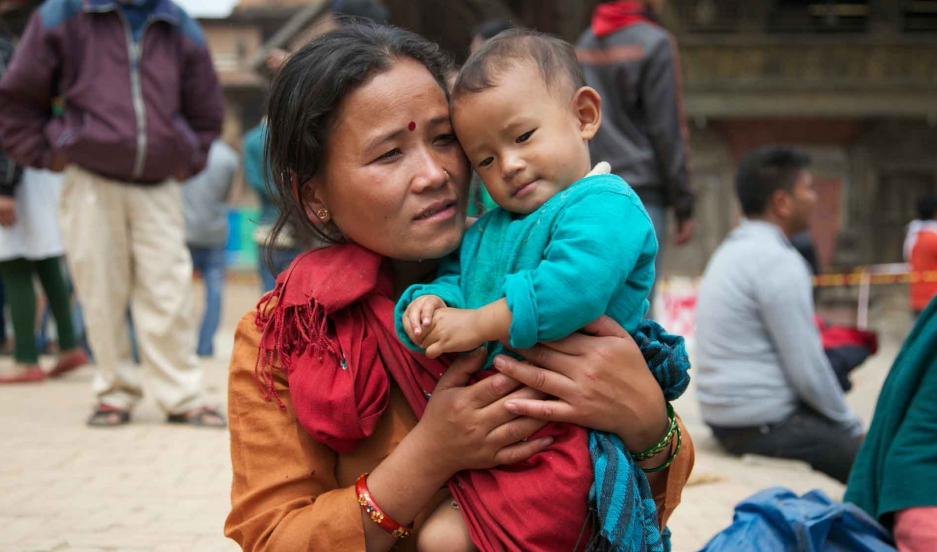 A mother with her son by Patan Durbar Square, a UNESCO World Heritage site, one day after the earthquake destroyed several temples.