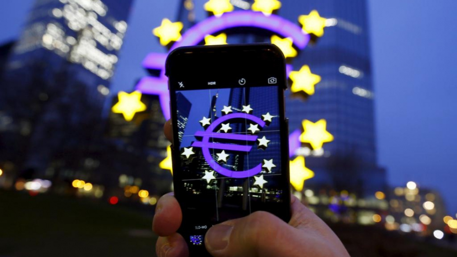 A tourist poses while taking a picture of the euro sign landmark outside the former headquarters of the European Central Bank in Frankfurt, Germany, on Jan. 19, 2016.