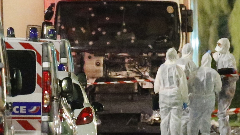 French police forces and forensic officers stand next to a truck