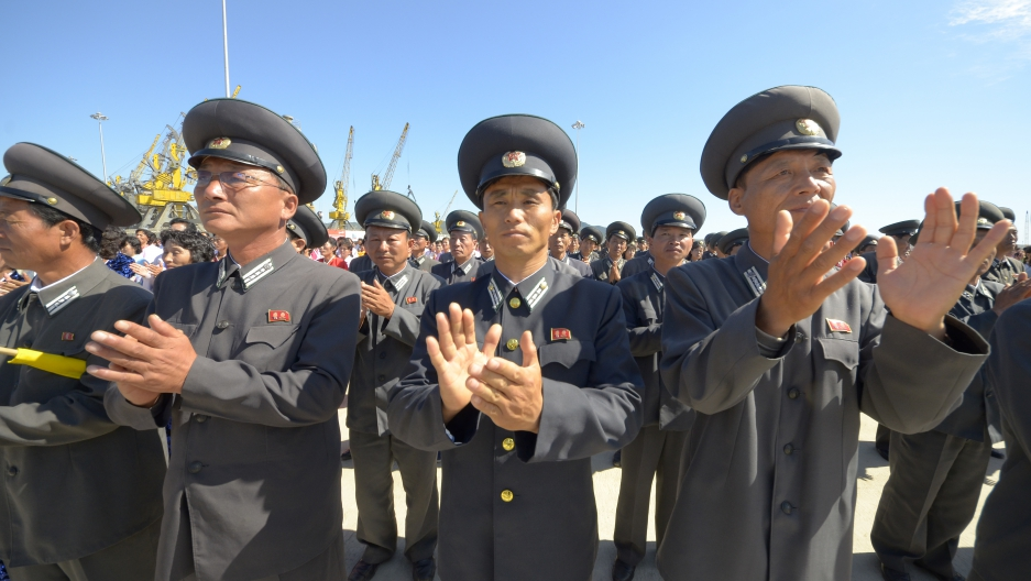 People applaud during a ceremony to mark the re-opening of a railway link between North Korea and Russia