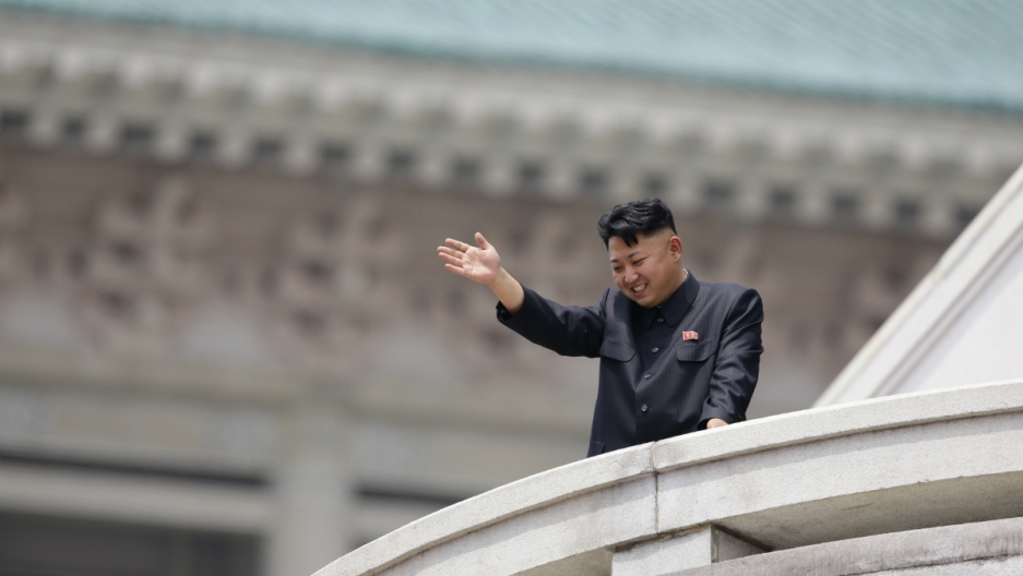 North Korean leader Kim Jong-un waves to the people during a parade in Pyongyang July 27, 2013.