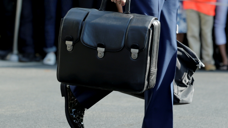 A military aide carrying a briefcase containing nuclear codes follows President Barack Obama on the South Lawn of the White House in Washington, DC, before his departure to Miami, Oct. 20, 2016.
