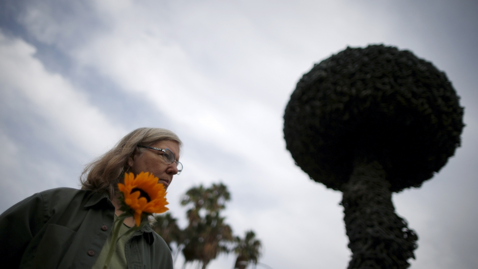 "Patricia Todd, 61, holds a sunflower at a peace vigil in front of ""Chain Reaction,"" a mushroom cloud sculpture created by Paul Conrad as a symbol of a world free of nuclear weapons, in Santa Monica, California, United States, September 21, 2015."