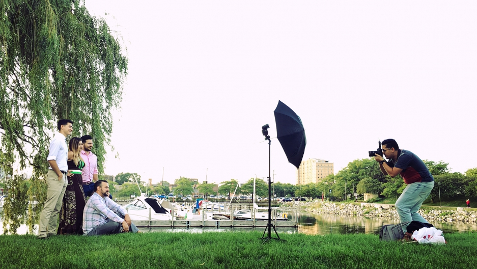 Photographer shoots family across green field