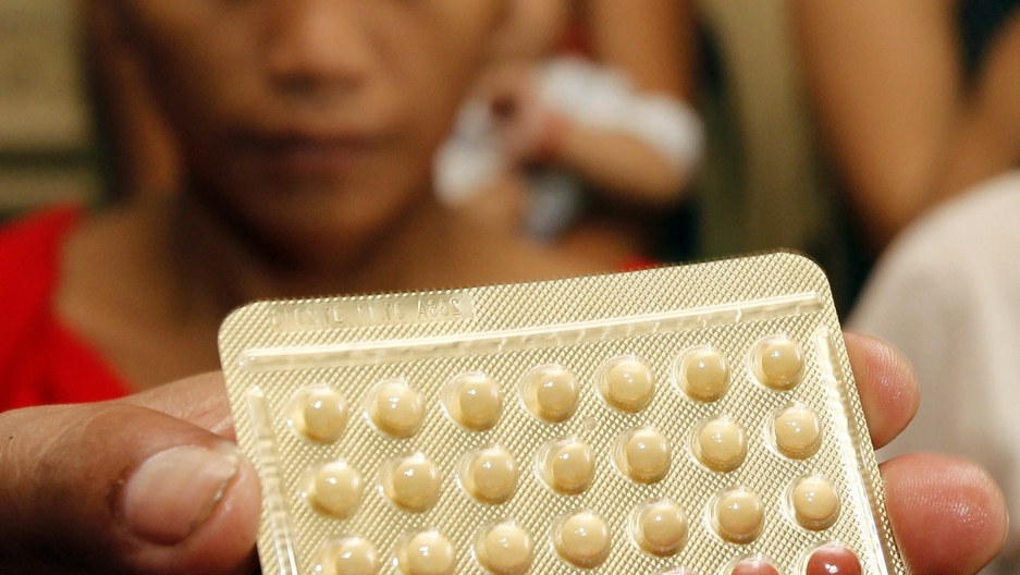 An NGO health worker holds contraceptive pills