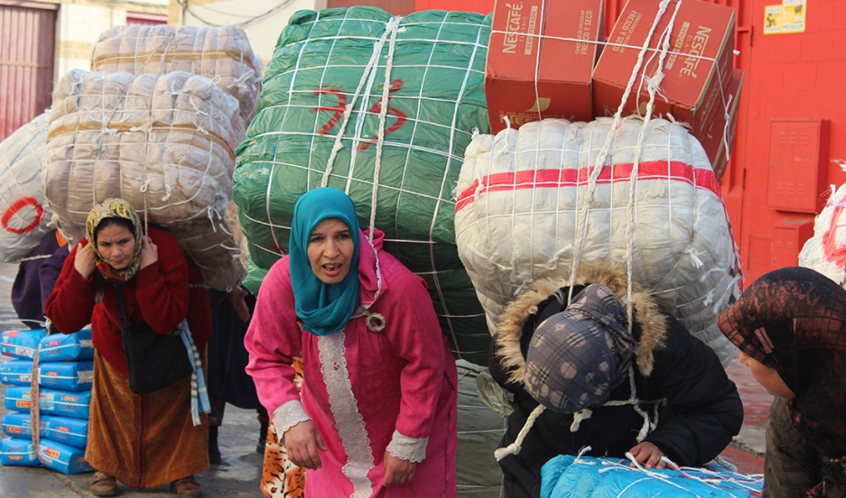 Moroccan women wait at a border crossing with loads of 100-200 pounds of commercial goods on their backs.