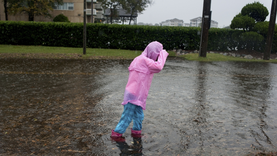 A child plays in the flooded streets of Norfolk, Virginia, during Hurricane Sandy in 2012. Norfolk is one of many coastal cities around the world experiencing more frequent flooding as sea levels rise in response to warmer global temperatures.