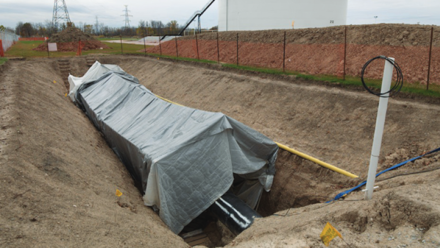 A section of Enbridge pipeline lies under a cover in a trench.