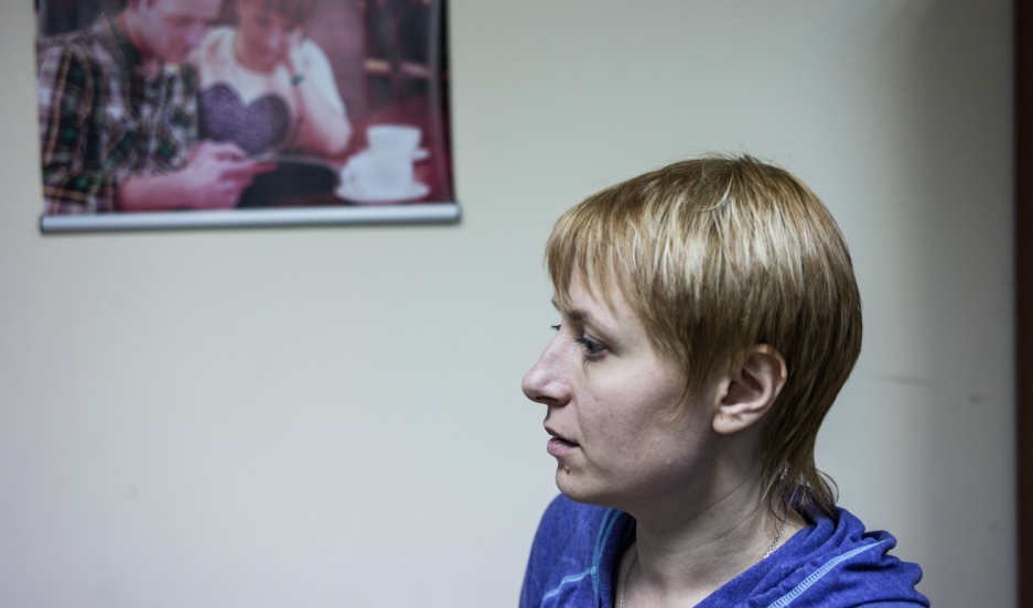 Waiting for news about her husband's fate, Svitlana Moroz stands in a Kiev NGO in front of a photograph showing her with her husband Aleksei in peaceful time.