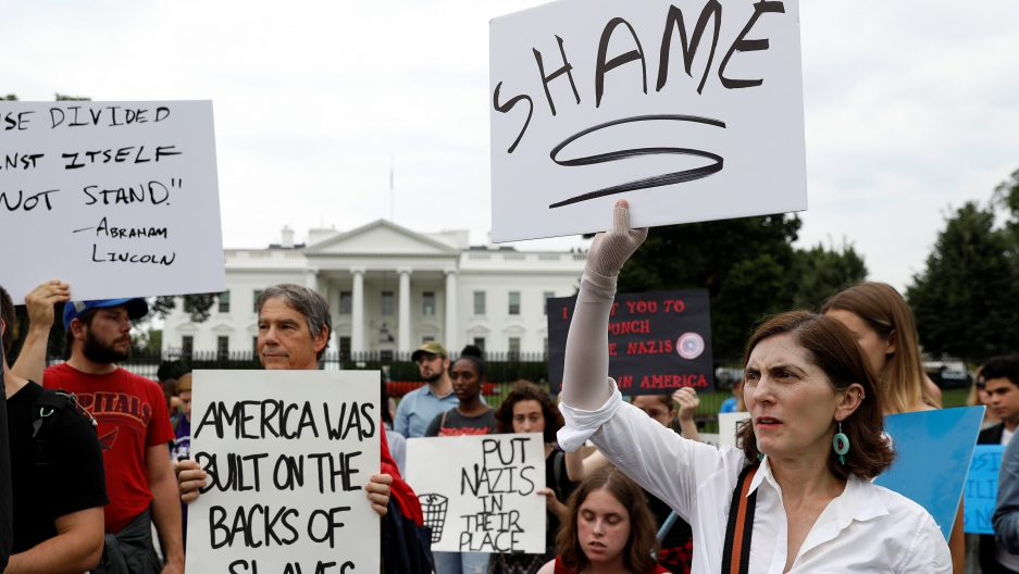 Protesters hold signs in front of the White House