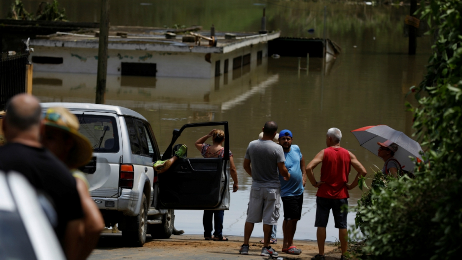 Local residents look at the flooded houses close to the dam of the Guajataca lake, on September 23, 2017.