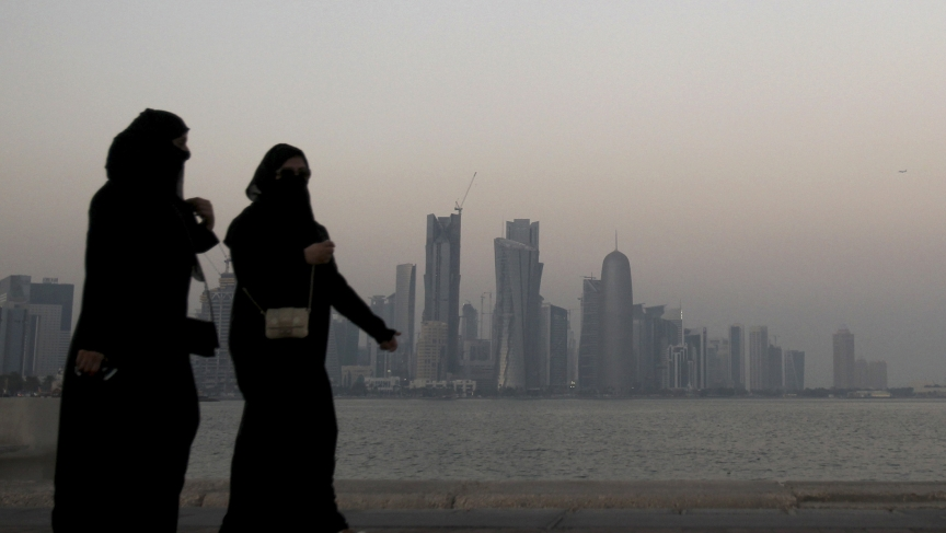 Women walk past buildings as the sun sets in Doha October 19, 2010.
