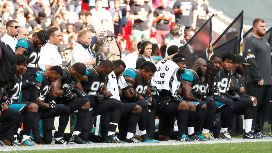 Jacksonville Jaguars players kneel during the US national anthem before their game against the Baltimore Ravens.