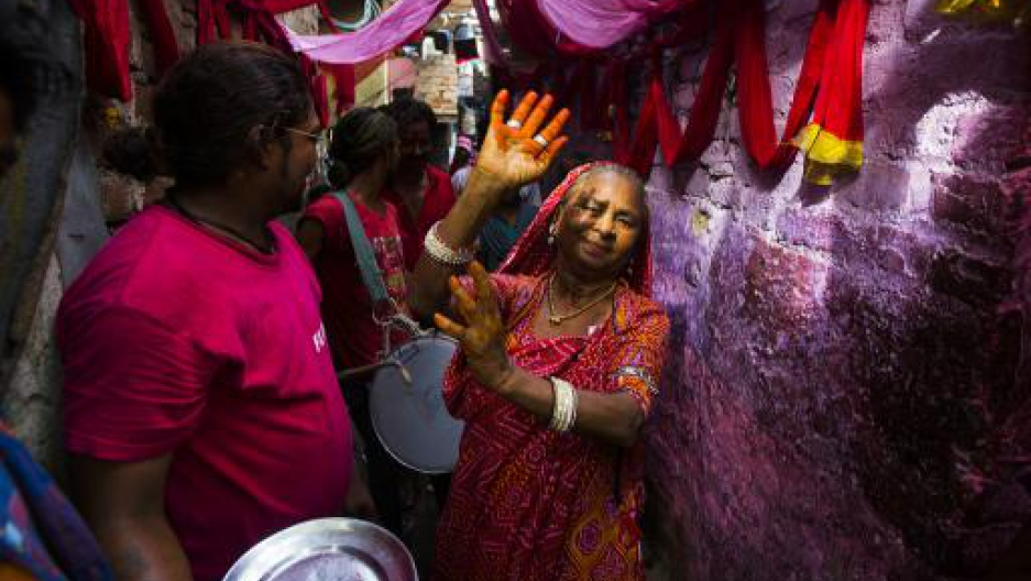 An Indian resident dances down an alleyway in front of drummers during a wedding procession in Kathputli Colony in New Delhi on June 7, 2013.