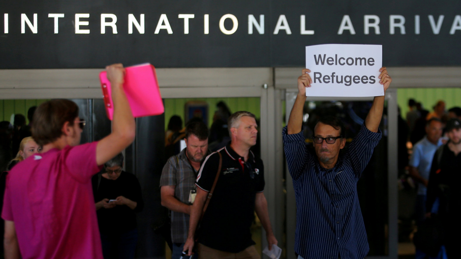 "Retired engineer John Wider, 59, is greeted by a supporter of President Donald Trump as he holds up a sign reading ""Welcome Refugees"" at the international arrivals terminal at Los Angeles International Airport in Los Angeles, California, on June 29, 2017."