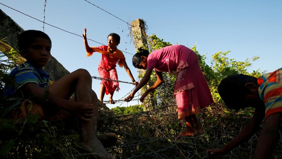 Rohingya children cross the Bangladesh-Myanmar border fence