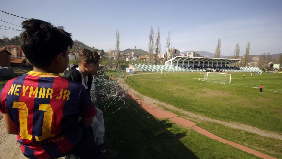 Roma community boys sit on the wall around Riza Lushta stadium as they watch the Kosovo's superleague soccer match between KF Trepca '89 and KF Istogu in Mitrovica, Kosovo, April 3, 2016.