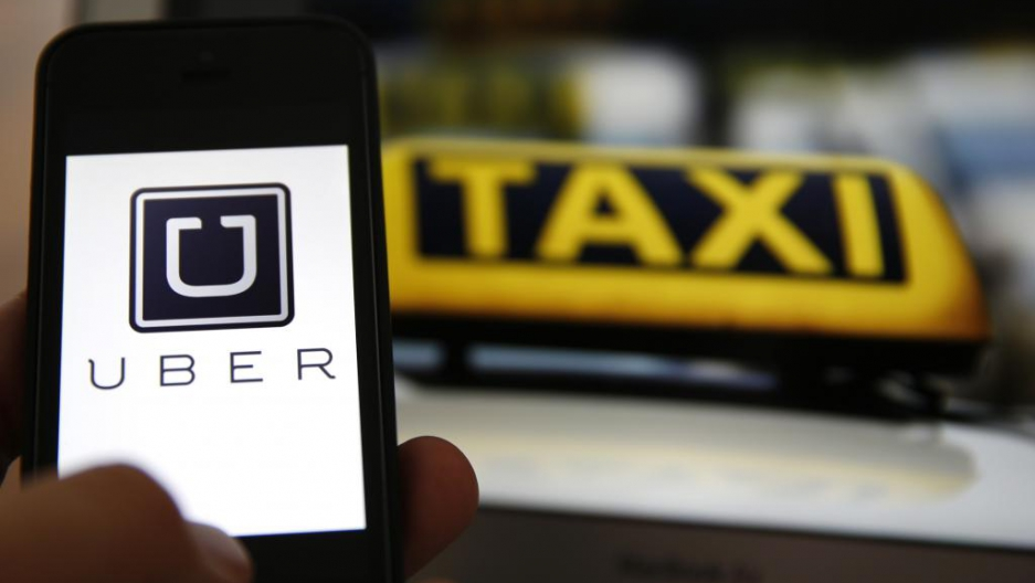 An illustration picture shows the logo of car-sharing service app Uber on a smartphone next to the picture of an official German taxi sign in Frankfurt, September 15, 2014.
