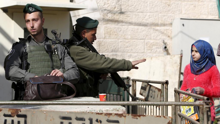 An Israeli border policeman gestures to Palestinians as another searches a bag in the West Bank city of Hebron