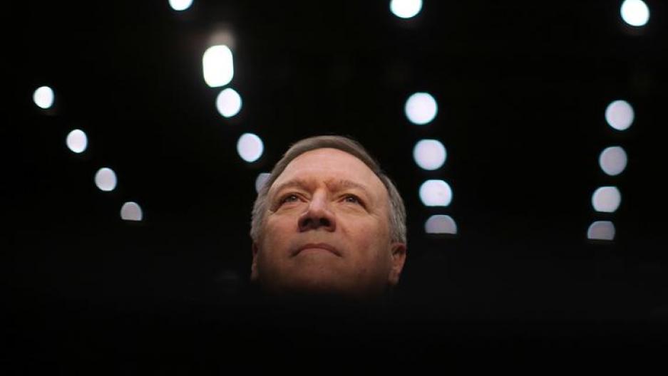 Portrait of man's head against rows of lights, dark around him