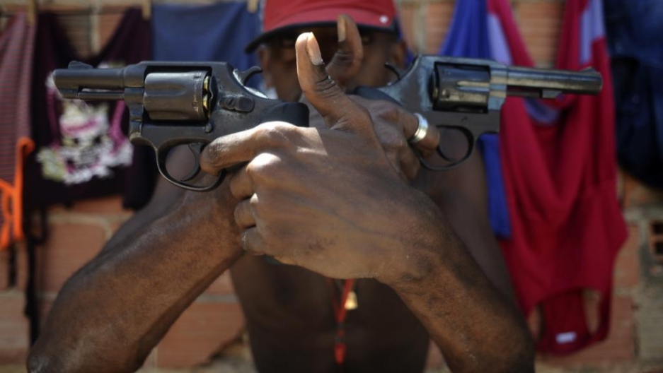 A Brazilian drug gang member nicknamed Pilintra, 26, poses with guns in Salvador.