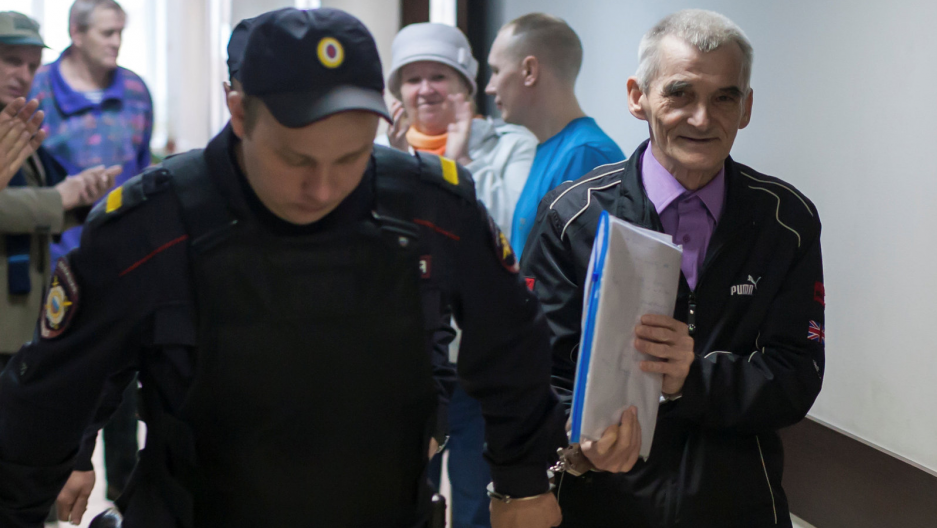 Historian Yuri Dmitriev accused of using his adopted daughter to produce child pornography, of illegally possessing a firearm and of depravity, is escorted by a police officer upon his arrival for a court hearing in Petrozavodsk, Russia, June 5, 2017.