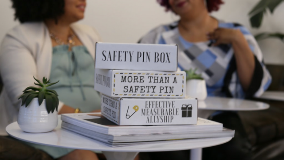 "Boxes on tables with labels: ""Safety pin box,"" ""More than a safety pin,"" ""Effective measurable allyship"""