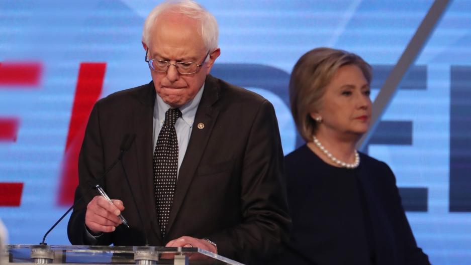 Democratic US presidential candidate Senator Bernie Sanders writes on his notes as his rival Hillary Clinton walks behind him