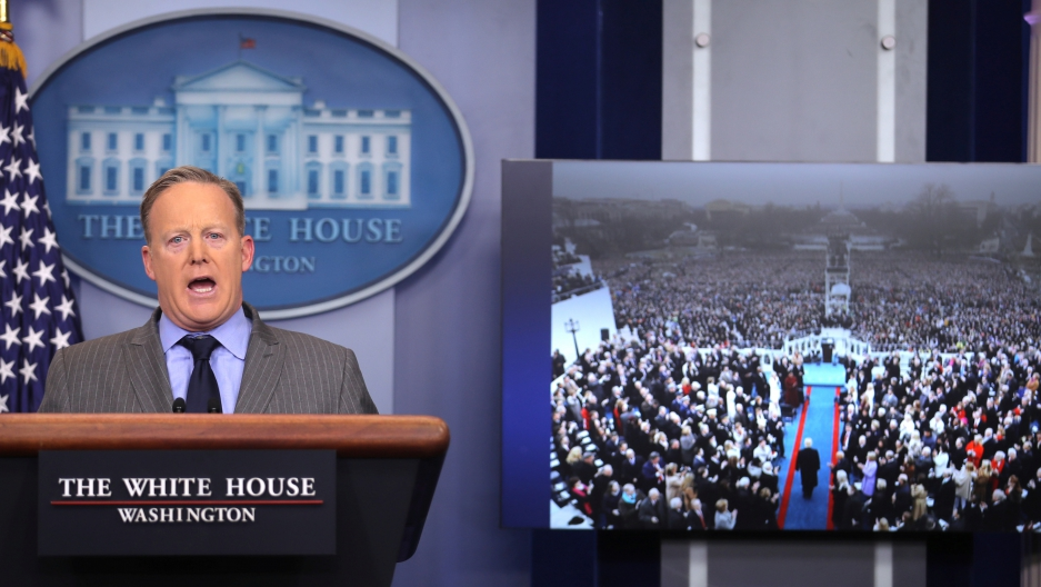Press Secretary Sean Spicer delivers a statement while television screen show a picture of U.S. President Donald Trump's inauguration