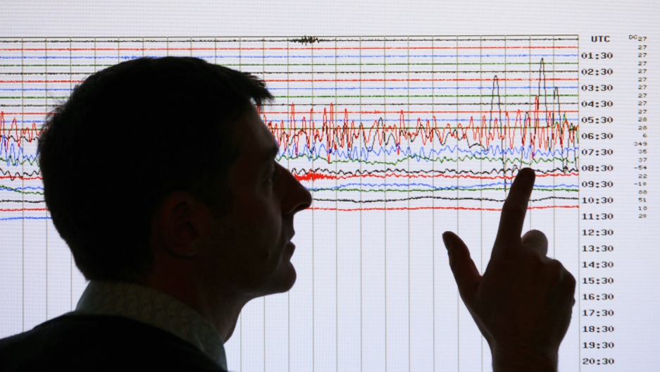 A seismologist poses for the media