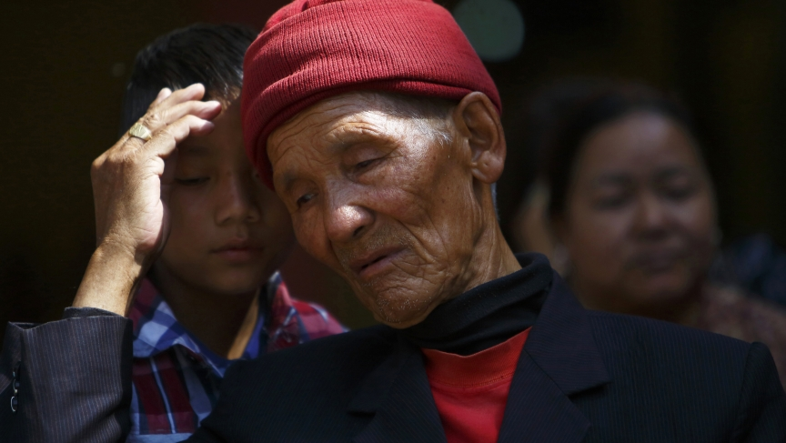 The father of Kaji Sherpa, one of 13 Nepali mountaineering guides who lost his life in an avalanche on Mount Everest, comforts his grandson as he waits for the body of his son to arrive at Sherpa Monastery in Kathmandu April 19, 2014.