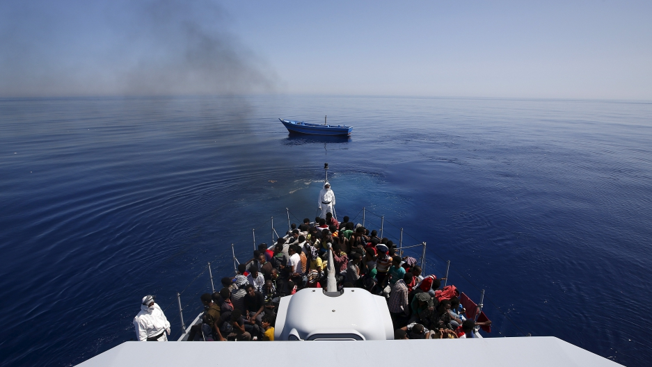 A group of 300 sub-Saharan Africans sit on board an Italian police vessel as their boat is left adrift off the coast of Sicily, May 14, 2015.